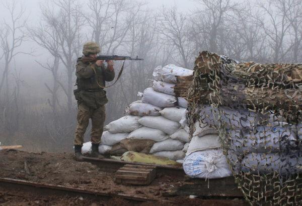 A Ukrainian soldier takes position on the front line at the town of Novoluhanske in the Donetsk region, Ukraine, Monday, Dec. 9, 2019. (Vitali Komar/ AP Photo)