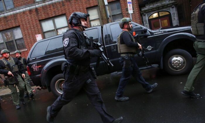 Police officers arrive to the scene where active shooting is happening in Jersey City. One officer was shot when two gunmen with a long rifle opened fire. Two suspects were barricaded in a convenience store, according to officials on Dec. 10, 2019. (Photo by Kena Betancur/AFP via Getty Images)