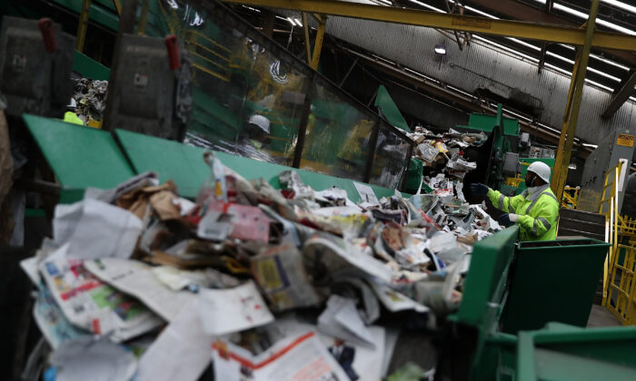 Workers sort recyclable materials as they pass through a sorting machine at Recology's Recylce Central in San Francisco, Calif., on Nov. 16, 2016. (Justin Sullivan/Getty Images)