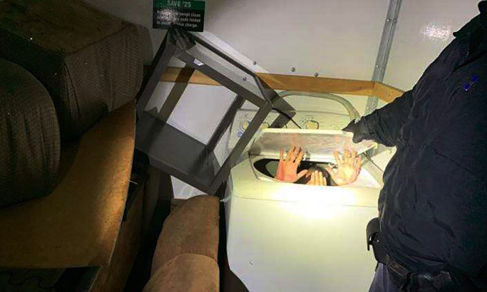 This photo released on Dec. 9, 2019 by U.S. Customs and Border Protection (CBP) shows hands held up by a person or persons hiding in a washing machine, among 11 Chinese nationals found by CBP agents hiding in furniture and appliances inside a moving truck stopped on Dec. 7 while entering the U.S. from Mexico at the San Ysidro border crossing near San Diego. (U.S. Customs and Border Protection via AP)