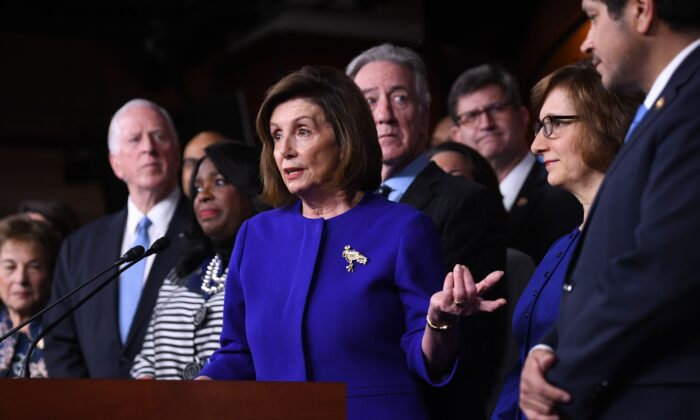 House Speaker Nancy Pelosi (D-Calif.) and House Ways and Means Committee Chairman Richard Neal, behind her, speak about the US - Mexico - Canada Agreement, known as the USMCA, on Capitol Hill in Washington, on Dec. 10, 2019. (Saul Loeb/AFP via Getty Images)