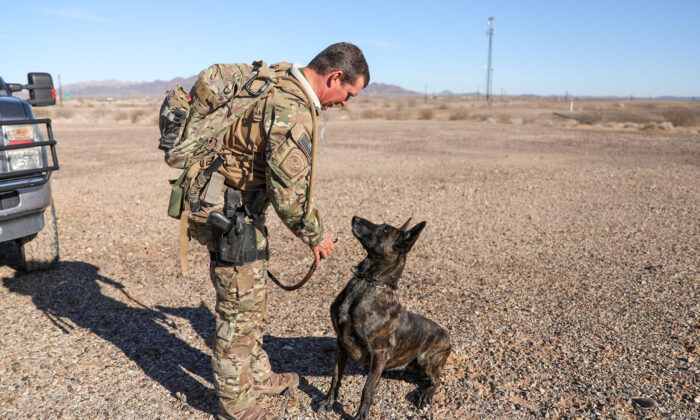 Border Patrol BORSTAR supervisory agent Chad Smith with his K-9 Kyra prepare for a training exercise near the Imperial Sand Dunes, Calif., on Nov. 30, 2019. (Charlotte Cuthbertson/The Epoch Times)