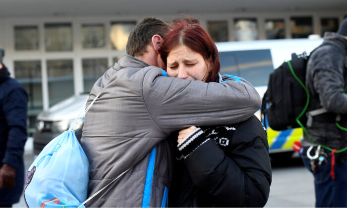 A man embraces a woman as she reacts outside the University Hospital, which was the site of a shooting, in Ostrava, Czech Republic, Dec. 10, 2019. (Radovan Stoklasa/Reuters)