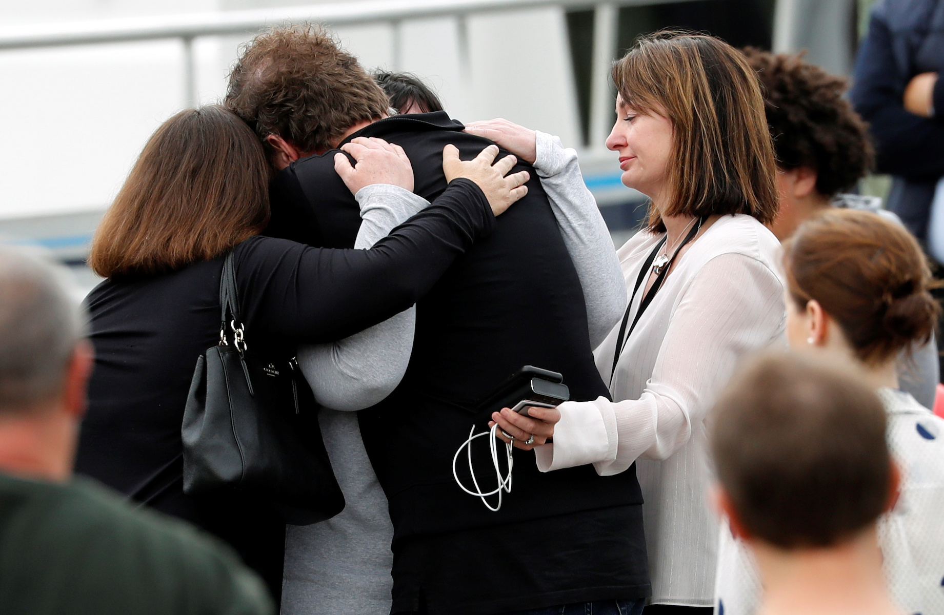 Relatives hug as they wait for rescue mission, following the White Island volcano eruption in Whakatane