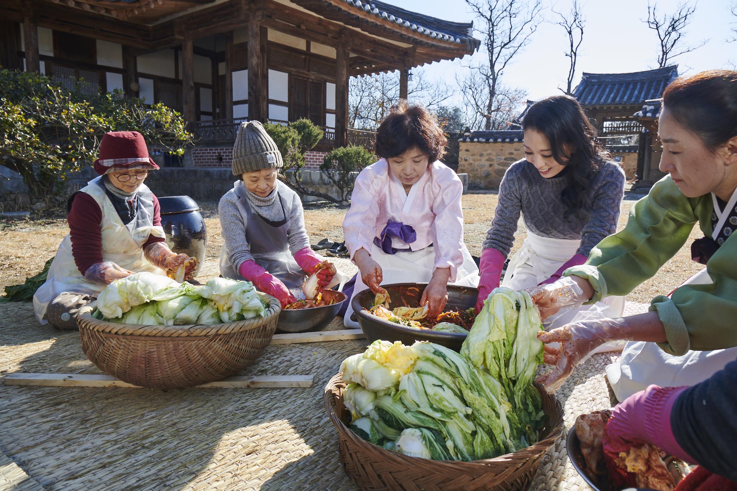group of korean women making kimchi