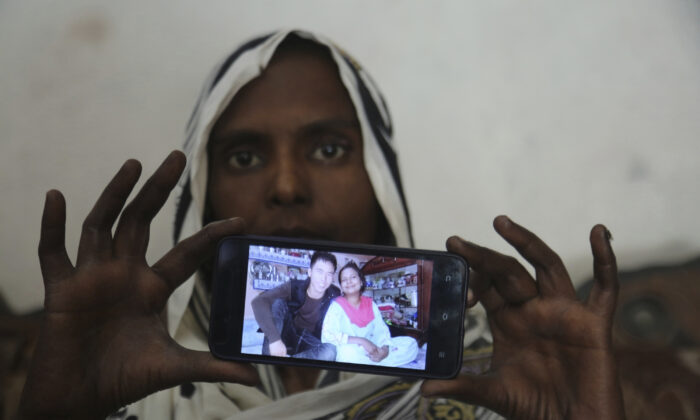 Pakistani Christian woman Samiya David shows her picture with Chinese husband, in Gujranwala, Pakistan. Samiya had been in China just two months when her brother got a phone call telling him to pick her up at the airport. When he arrived, he found Samiya in a wheelchair, malnourished and too weak to walk, said her cousin Pervaiz Masih. She died barely five weeks later. Masih was among the relatives who prepared Samiya's grave and attended her burial in May. (K.M. Chaudary/AP Photo)