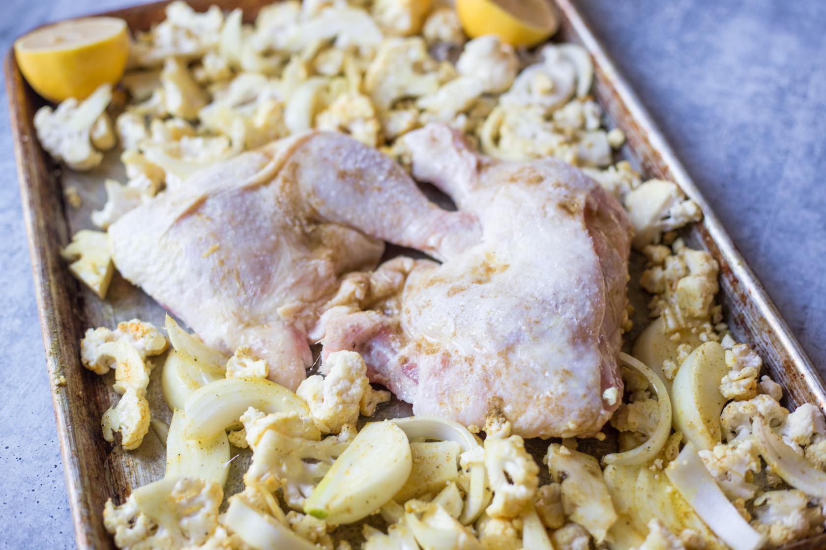 raw chicken thighs and cauliflower on a sheet pan