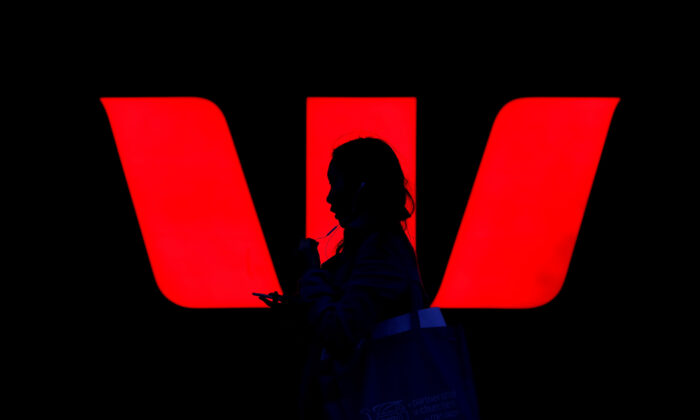A woman walks past an illuminated logo for Australia's Westpac Bank in Sydney, Australia, on Sept. 6, 2017.   (Reuters/Steven Saphore/File Photo)