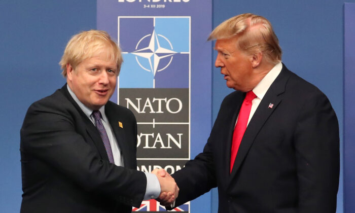 British Prime Minister Boris Johnson shakes hands with U.S. President Donald Trump onstage during the annual NATO heads of government summit in Watford, England, on Dec. 4, 2019. (Steve Parsons-WPA Pool/Getty Images)