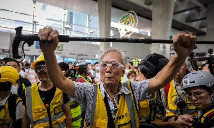 "This picture taken on Sept. 7, 2019 shows ""Grandpa Wong"" (C), 85, shielding protesters from the police by holding his walking stick up along with other ""silver hair"" volunteers in the Tung Chung district in Hong Kong. Despite his age, Wong is a regular sight at Hong Kong's street battles, hobbling towards police lines, placing himself in between riot officers and hardcore protesters, hoping to de-escalate what have now become near daily clashes. (Vivek Prakash/AFP via Getty Images)"