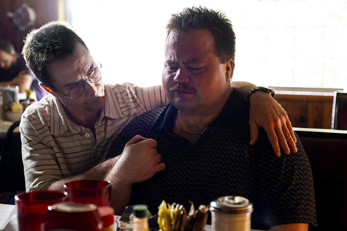man comforts crying man at diner