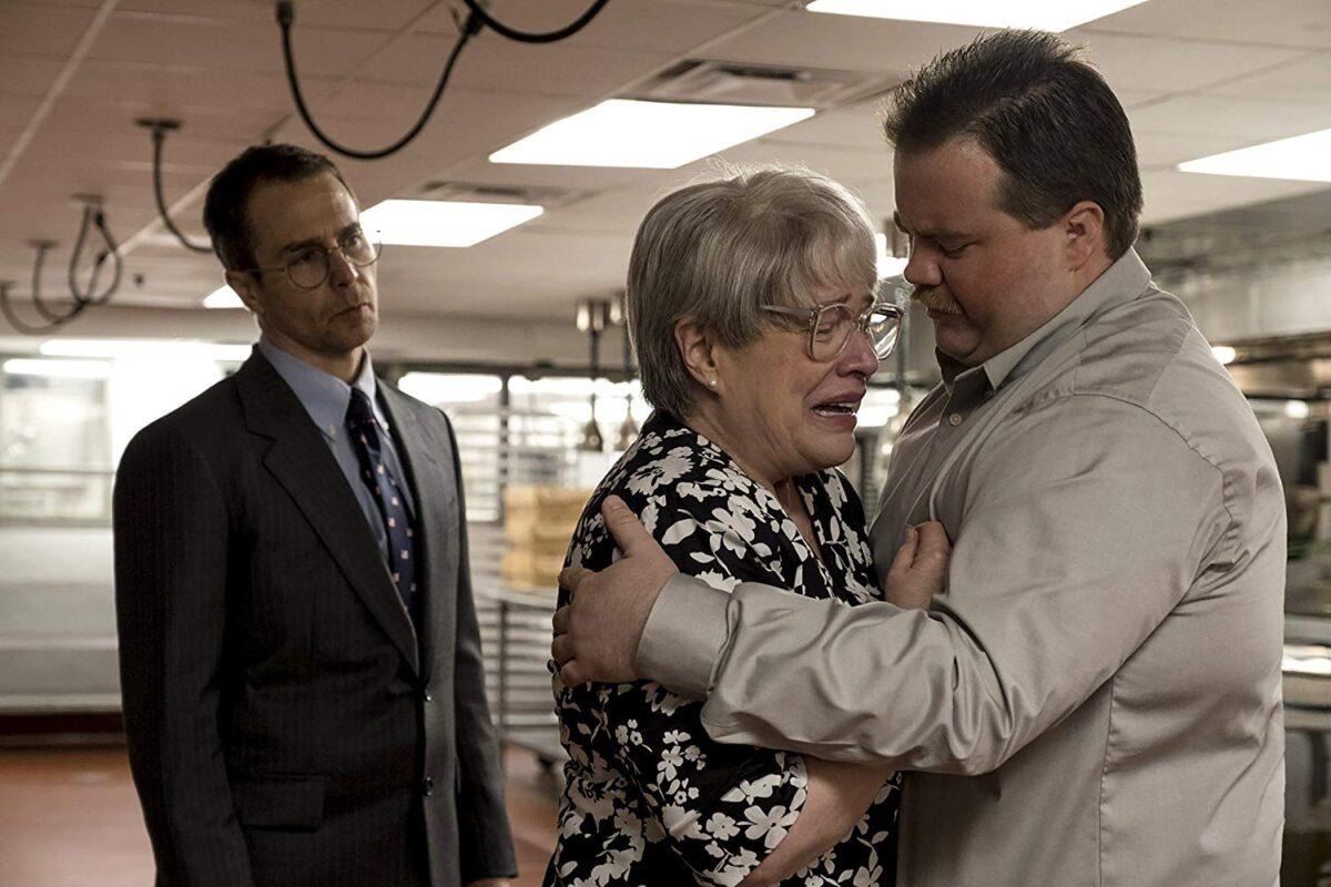 man hugs woman, man in suit looks on