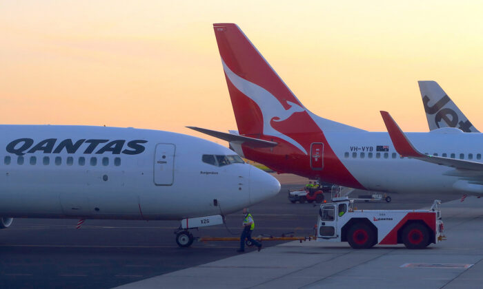 Workers are seen near Qantas Airways, Australia's national carrier, Boeing 737-800 aircraft on the tarmac at Adelaide Airport, Australia, on Aug. 22, 2018. (Reuters/David Gray)