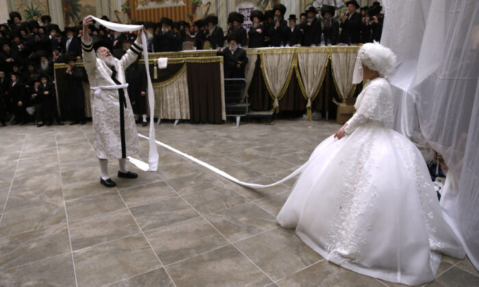 Rabbi Meir Rosenboim (L) of the Premishlan Hasidic dynasty dance in front of his daughter Hana Ritza during the Mitzvah Tantz, a Hasidic custom is which the men dance before the bride on the wedding night, on Dec. 9, 2019 after a wedding feast in the Israeli religious city of Bnei Brak near Tel Aviv. (Menahem Kahana/AFP via Getty Images)