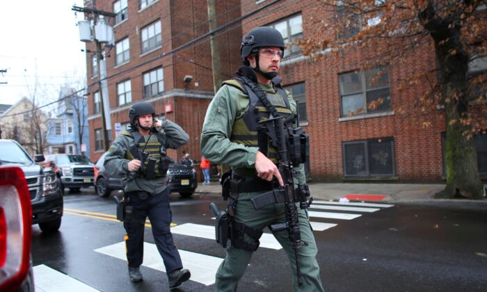 Police officers arrive on the scene during a shooting at JC Kosher Supermarket in Jersey City on Dec. 10, 2019, that left five dead, including the two armed suspects. The suspects had earlier shot a police officer. (Kena Betancur/AFP via Getty Images)