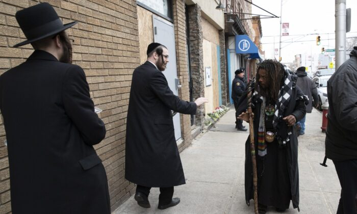 Robert McClain (R), offers condolences to two Jewish men, on Dec. 13, 2019 in Jersey City, N.J. close to the site where three people and two gunmen were shot. (AP Photo/Mark Lennihan)