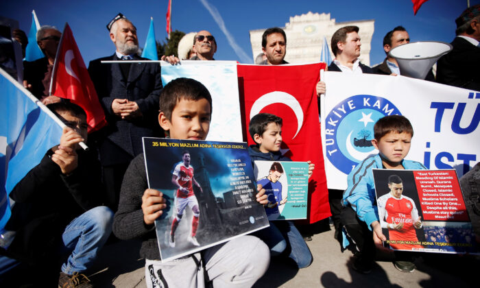 "Ethnic Uyghur boys hold placards with pictures of English soccer club Arsenal's midfielder Mesut Ozil during a protest against China in Istanbul, Turkey on Dec. 14, 2019. The placard reads: ""Thank you, Mesut Ozil, on behalf of 35 million oppressed.""  (Kemal Aslan/Reuters)"