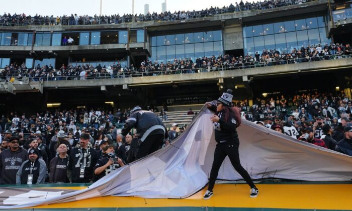 Fans rip banners from the stadium walls after the Oakland Raiders loss to the Jacksonville Jaguars at RingCentral Coliseum in Oakland, California on Dec. 15, 2019. (Daniel Shirey/Getty Images)