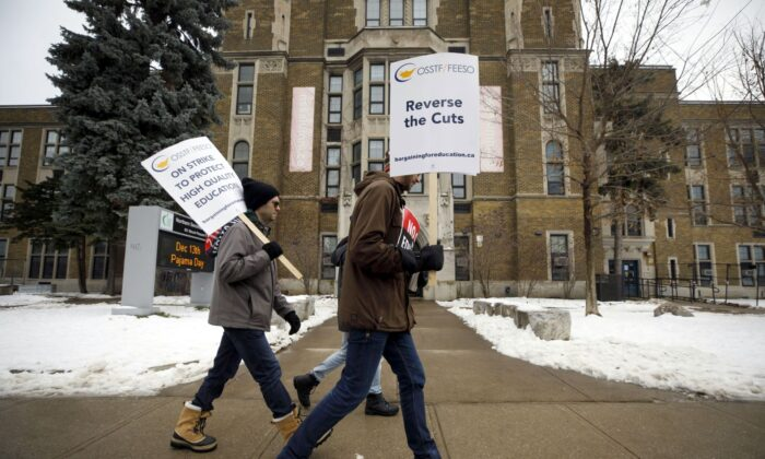 Striking teachers of the Ontario Secondary School Teachers' Federation walk the picket line outside Northern Secondary School in Toronto on Dec. 4, 2019. (The Canadian Press/Cole Burston)
