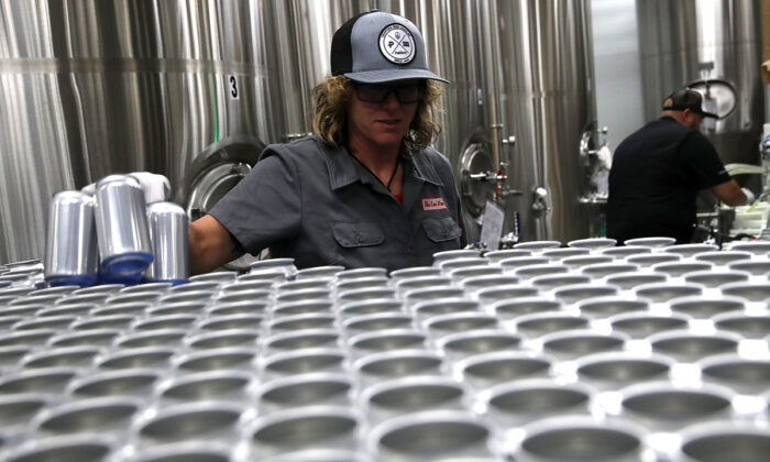 Kathryn Fisher with Can Van, a mobile canning company, places empty aluminum cans on a conveyor belt to be filled with beer at Devil's Canyon Brewery in San Carlos, Calif., on June 6, 2018. (Justin Sullivan/Getty Images)