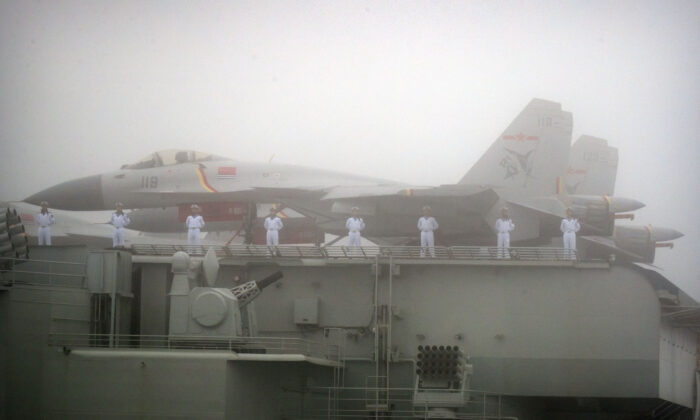 Sailors stand near fighter jets on the deck of the Chinese People's Liberation Army (PLA) Navy aircraft carrier Liaoning as it participates in a naval parade to commemorate the 70th anniversary of the founding of China's PLA Navy in the sea near Qingdao, in eastern China's Shandong Province on April 23, 2019. (Mark Schiefelbein/AFP via Getty Images)