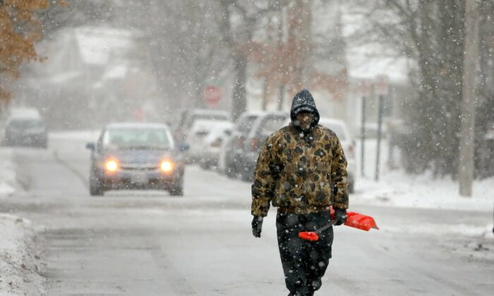 Bill Parham walks down an icy street in Maplewood, Mo., looking to clear snow off people's driveways and sidewalks on Dec. 16, 2019. (David Carson/St. Louis Post-Dispatch via AP)