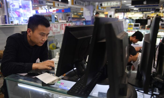 A man repairs a laptop in a computer mall in Beijing on March 30, 2018. (GREG BAKER/AFP via Getty Images)