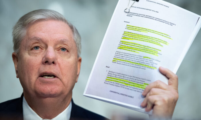 Chairman of the Senate Judiciary Committee Lindsey Graham (R-S.C.) holds a copy of the Steele Dossier during a Senate Judiciary Committee hearing on Capitol Hill on Dec. 11, 2019. (Saul Loeb/AFP via Getty Images)