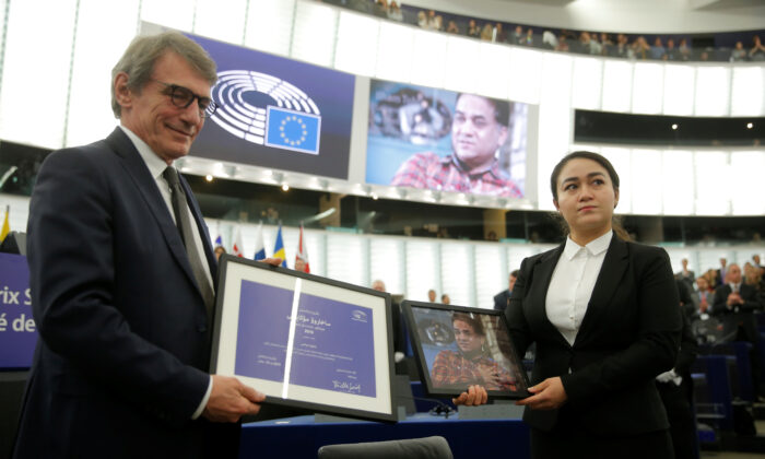European Parliament President David-Maria Sassoli stands next to Jewher Ilham, daughter of Ilham Tohti, Uyghur economist and human rights activist, holding a portrait of her father during the award ceremony for his 2019 EU Sakharov Prize next to at the European Parliament in Strasbourg, France on Dec. 18, 2019.  (Vincent Kessler/Reuters)