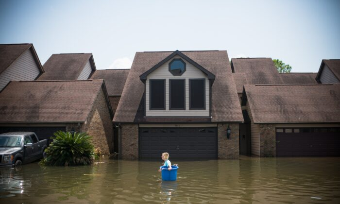 Jenna Fountain carries a bucket down Regency Drive to try to recover items from her flooded home after Hurricane Harvey, in Port Arthur, Texas, on Sept. 1, 2017.   (EMILY KASK/AFP via Getty Images)