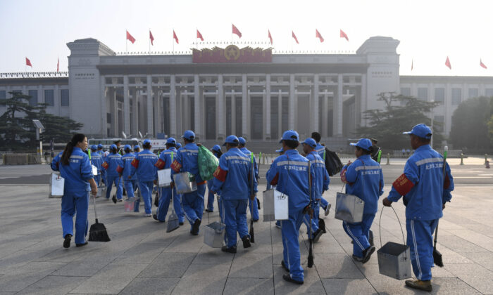 Sanitation workers walk before a wreath-laying ceremony for Martyr's Day at Tiananmen Square in Beijing, China on Sep. 30, 2019. (Madoka Ikegami/Pool/AFP via Getty Images)