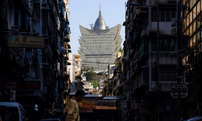 A pedestrian walks in a residential neighborhood in front of a view of the Grand Lisboa casino resort (back C) in Macau, on August 29, 2017. (Anthony Wallace/AFP via Getty Images)