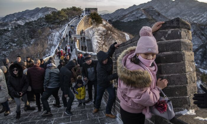 Tourists struggle to climb in the wind on an icy section of the Great Wall at Badaling in Beijing, China, on Nov. 30, 2019. (Kevin Frayer/Getty Images)