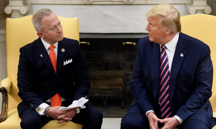 Rep. Jeff Van Drew (NJ), who is switching from the Democratic Party to the Republican Party, listens to US President Donald Trump during a meeting in the Oval Office of the White House on Dec. 19, 2019, in Washington, DC. (Photo by Brendan Smialowski/AFP/Getty Images)