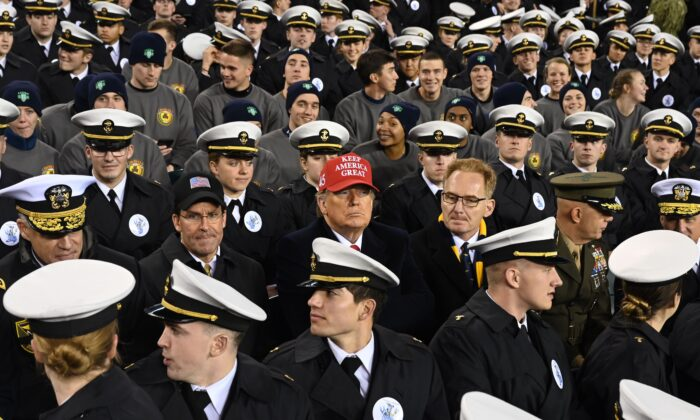 President Donald Trump, center, with U.S. Defense Secretary Mark Esper, center-left, and Acting United States Secretary Thomas Modly, center right, joins Naval Academy cadets during the the Army versus Navy American Football game in Philadelphia, Pa., on Dec. 14, 2019. (Andrew Caballero-Reynolds/AFP via Getty Images)