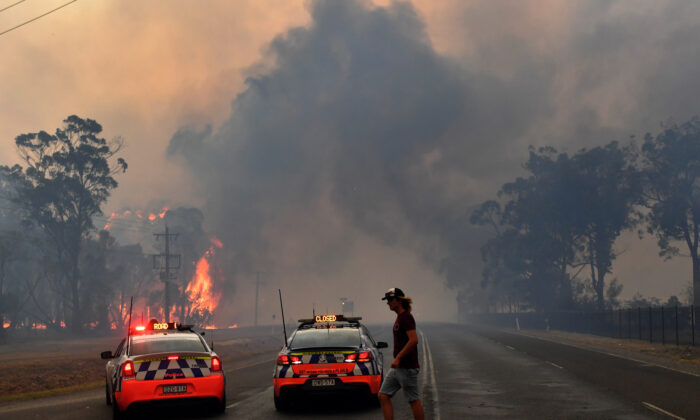 Police block the Old Hume Highway as a blaze jumps the road near the town of Tahmoor as the Green Wattle Creek Fire threatens a number of communities in the south west of Sydney, Australia, Dec. 19, 2019. (AAP Image/Dean Lewins/via Reuters)