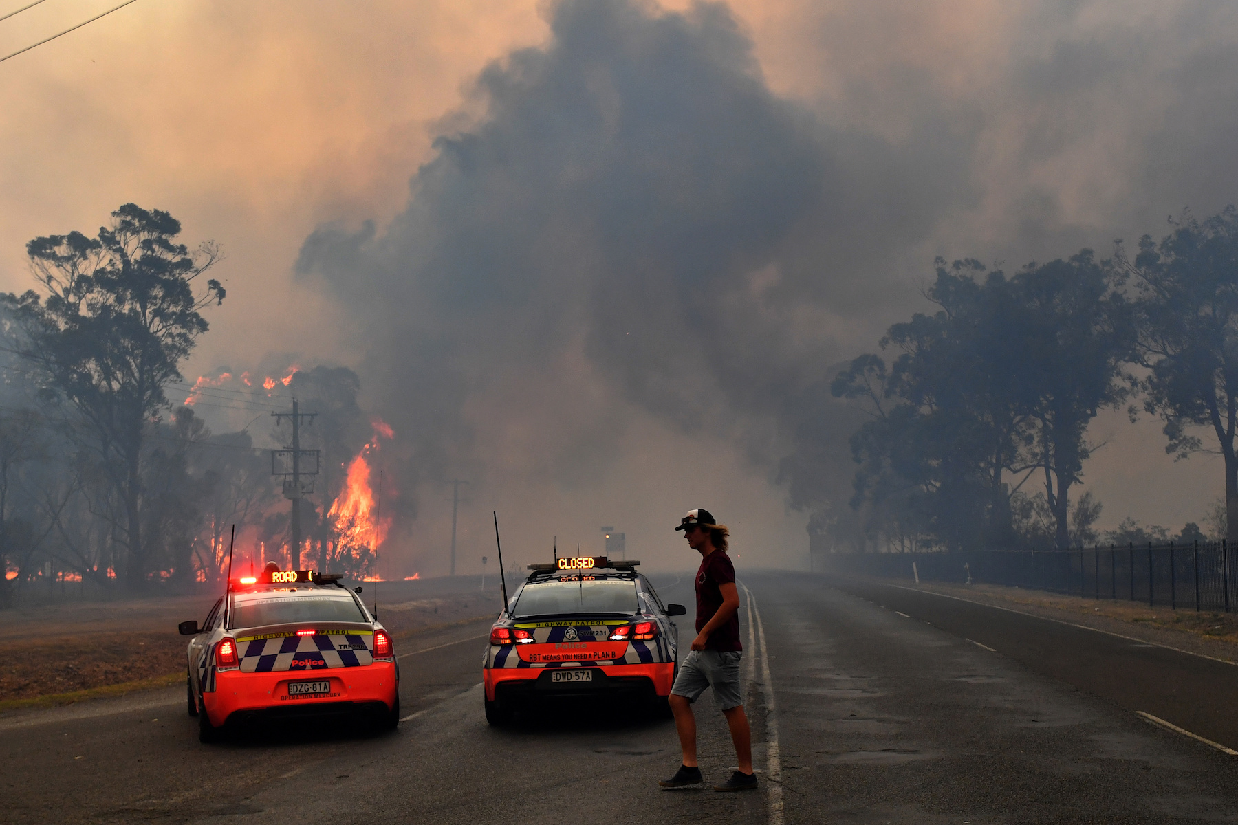 Police block the Old Hume Highway as a blaze jumps the road near the town of Tahmoor as the Green Wattle Creek Fire threatens a number of communities in the south west of Sydney
