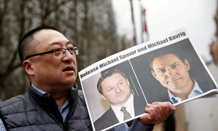 A man holds a placard calling for China to release Canadian detainees Michael Spavor and Michael Kovrig outside a court hearing for Huawei executive Meng Wanzhou at the B.C. Supreme Court in Vancouver on March 6, 2019. (Lindsey Wasson/Reuters)