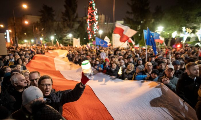 People deploy a giant national flag during a demonstration in front of Polish parliament against a judicial reform pushed by lawmakers of the ruling Law and Justice party PiS on Dec. 18, 2019 in Warsaw. (Wojtek Radwanski/AFP via Getty Images)