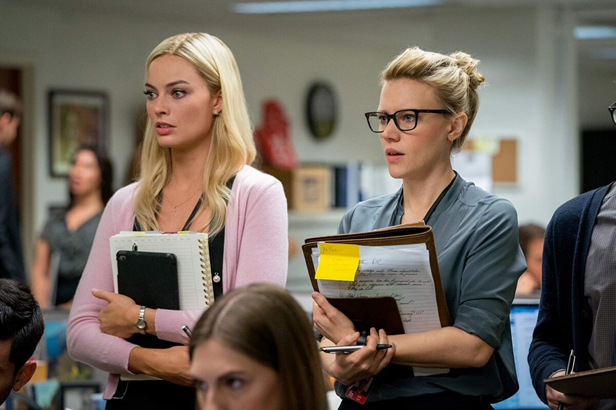 Two blond women with clipboards in office
