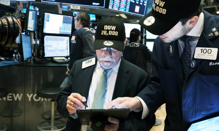 "Traders wear ""DOW 28,000"" hats on the floor of the New York Stock Exchange (NYSE) in New York on Nov. 15, 2019. (Spencer Platt/Getty Images)"