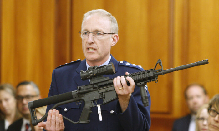 New Zealand's Police acting superintendent Mike McIlraith shows New Zealand lawmakers an AR-15 style rifle similar to one of the weapons a gunman used to slaughter 51 people at two mosques, in Wellington, New Zealand, on April 2, 2019. (AP Photo/Nick Perry, File)