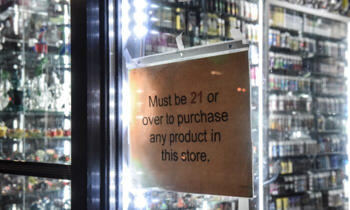 """A sign that states """"must be over 21"""" hangs in the store window of a vape shop in New York City on Dec. 19, 2019. (Stephanie Keith/Getty Images)"""