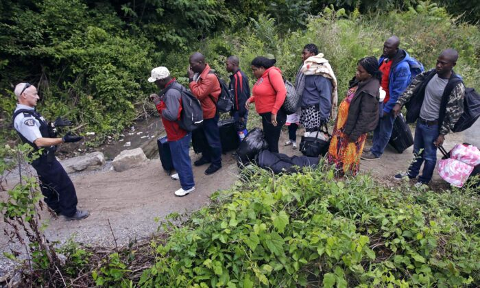 An RCMP officer standing in Saint-Bernard-de-Lacolle, Quebec, advises migrants who arrived from Champlain, N.Y., via Roxham Road that they are about to illegally cross into Canada and will be arrested, on Aug. 7, 2017. (AP Photo/Charles Krupa)