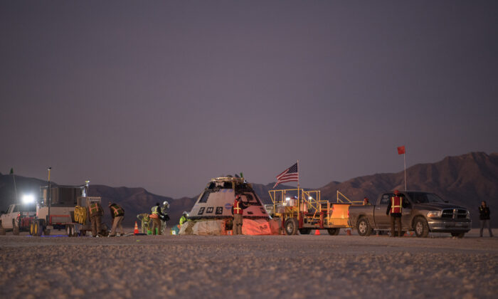 Boeing, NASA, and U.S. Army personnel work around the Boeing Starliner spacecraft shortly after it landed in White Sands, N.M., on Dec. 22, 2019. (Bill Ingalls/NASA via AP)