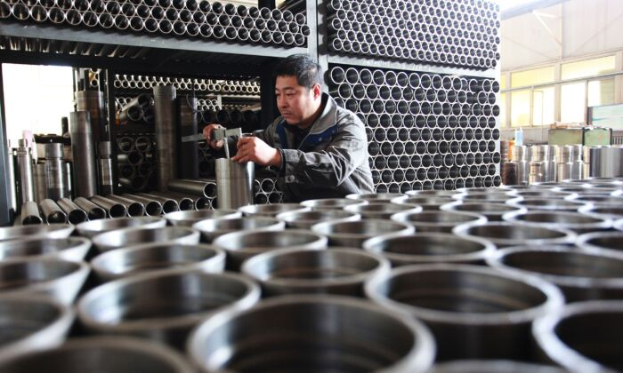 A worker is checking drilling tool components at a factory in Xuanhua city in China's northern Hebei province on December 18, 2019. (STR/AFP via Getty Images)
