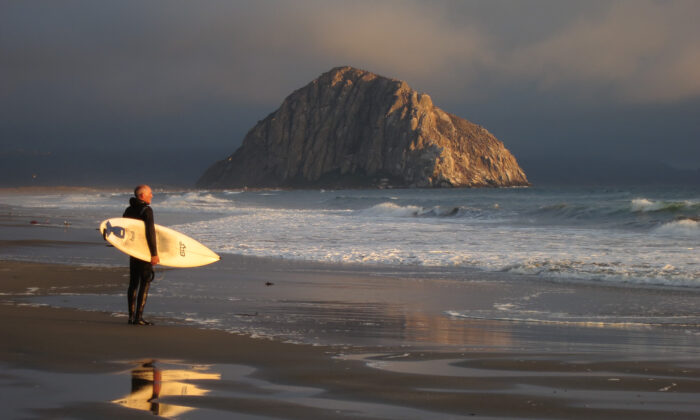 A surfer looks out at the Pacific Ocean as Morro Rock stands under evening sun in Morro Bay, Calif., on July 8, 2014. (Sean Gallup/Getty Images)