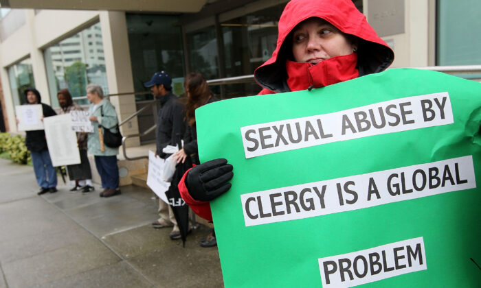 A protester holds a sign in a demonstration with members of the group SNAP, the Survivors Network of those Abused by Priests, outside of the offices of the San Francisco Archdiocese in San Francisco, Calif., on March 29, 2010. (Justin Sullivan/Getty Images)