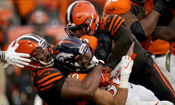 Denver Broncos running back Phillip Lindsay, center, is tackled by Cleveland Browns defensive tackle Sheldon Richardson, left, during the second half of NFL football game in Denver on Nov. 3, 2019. (Jack Dempsey/AP-File)