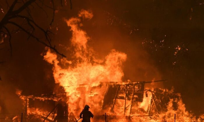 NSW RuralFireService crews fight the Gospers MountainFireas it impacts a structure at Bilpin, Austalia on Dec. 21, 2019. (Dan Himbrechts/AAP Images via AP)